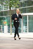 Business woman walking outdoors and talking on mobile phone Stock Photo
