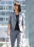 Business woman walking and smiling in the city Stock Photography
