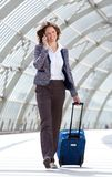 Business woman walking at station with bag and mobile phone Royalty Free Stock Photography