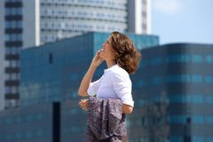 Business woman walking and talking on cell phone in the city Stock Photography