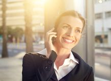 Business woman walking and talking on mobile phone Stock Photos