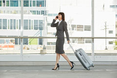 Business woman walking and talking on mobile phone with suitcase. Portrait of business woman walking and talking on mobile phone with suitcase Royalty Free Stock Photography