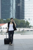 Business woman walking and using a mobile phone Royalty Free Stock Image