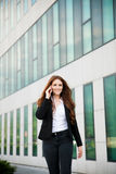Business woman walks outdoor with smartphone talking to her team Royalty Free Stock Photos