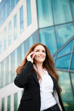 Business woman walks outdoor with smartphone talking to her team Stock Photos
