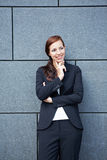 Business woman on wall thinking Stock Photography