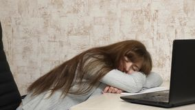 Business woman was weakened at work and fell asleep at a computer. A tired office worker sleeps on documents at her desk. Business woman was weakened at work and stock footage