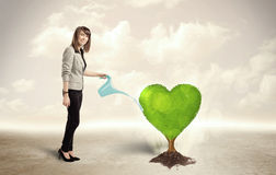 Business woman watering heart shaped green tree Stock Photo