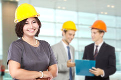 Business woman wear a safety helmet. with team mate at the backg Stock Image