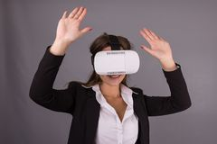 Business Woman in wearable technology VR glasses. Confident young woman in a business suit in virtual reality headset Stock Photos