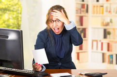 Business woman wearing glasses sitting by computer desk looking at piece of paper with shocked facial expression Royalty Free Stock Images