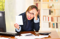 Business woman wearing glasses sitting by computer desk looking at piece of paper with shocked facial expression Stock Image
