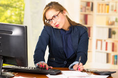 Business woman wearing glasses sitting by computer desk working and talking on phone, mobile squeezed between shoulder Stock Images