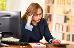 Business woman wearing glasses sitting by desk with computer expressing mild frustration Royalty Free Stock Image