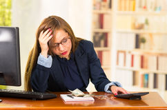 Business woman wearing glasses sitting by desk with computer expressing mild frustration, money, papers and calculator Royalty Free Stock Photo