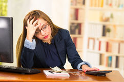 Business woman wearing glasses sitting by desk with computer expressing mild frustration, money, papers and calculator Royalty Free Stock Photos