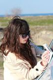 Business woman wearing glasses, writing in a notebook near the c. Business girl in sunglasses, writes in a notebook near the car Royalty Free Stock Photography
