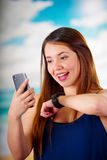 Business woman wearing in her wrist a smart watch with voice control and using her cellphone, in a sunny day background.  stock photo