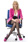 Business Woman Wearing Pink Sitting in an Office Chair Royalty Free Stock Photos