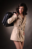business woman wearing a raincoat and suitcase Stock Photos