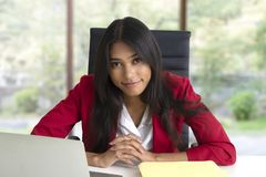 Business woman wearing red suit with friendly smile stock photo