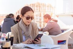 Business woman wearing sunglasses looking at cell phone in hands stock photography