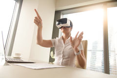 Business woman wearing virtual reality glasses. Business woman in office wearing virtual reality glasses and interacts with digital simulation. Female office Royalty Free Stock Photos