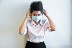 Business woman wear hygiene mask and sick. Business woman wears a green hygiene face mask and think inside her head while feels sick Royalty Free Stock Images