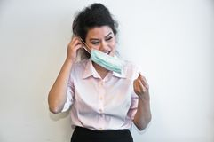 Business woman wear hygiene mask and sick. Business woman wears and then takes off a face hygiene mask and feels sick Royalty Free Stock Photography