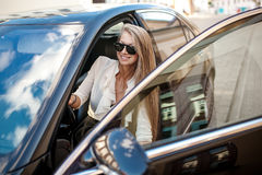Business woman in white blouse and black skirt sitting in a blac. Pretty blond woman in white blouse and black skirt sitting in a black car with one leg out Stock Photo