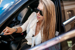 Business woman in white blouse and black skirt sitting in a blac. Pretty blond woman in white blouse and black skirt sitting in a black car with one leg out Stock Photography