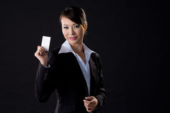 Business woman with white card. Asian business woman with white card on black background Royalty Free Stock Photography