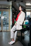 Business woman in white coat and trousers clothing store royalty free stock photography