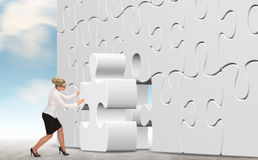 Business woman with a white puzzle on sky background. Stock Images