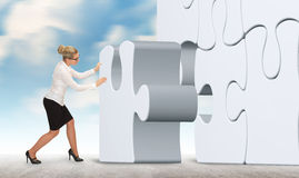Business woman with a white puzzle on sky background. Royalty Free Stock Photo