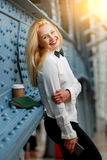 Business woman in white shirt, black pants at blue wall Stock Photos