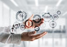 Cogwheels and gears mechanism as social communication concept. Business woman in white shirt keeping black social gear icons in hands with office view on Royalty Free Stock Photography