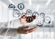 Cogwheels and gears mechanism as social communication concept. Business woman in white shirt keeping black social gear icons in hands with office view on Royalty Free Stock Photo