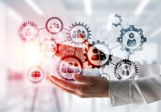 Cogwheels and gears mechanism as social communication concept. Business woman in white shirt keeping black social gear icons in hands with office view and Stock Images