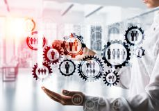 Cogwheels and gears mechanism as social communication concept. Business woman in white shirt keeping black social gear icons in hands with office view and Royalty Free Stock Photos