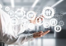 Cogwheels and gears mechanism as social communication concept. Business woman in white shirt keeping white social gear icons in hands with office view on Stock Image
