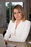 Business woman. In white suit behind laptop Royalty Free Stock Photos