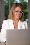 Business woman in white suit. Business woman siting behind laptop Stock Photos