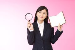 Woman with a magnifying glass. Business woman who checks the schedule Royalty Free Stock Photography