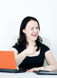 Business woman winking and showing thumbs up Stock Photo