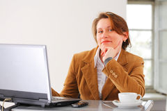 Business woman at work. Portraite of a young smiling business woman at her working place Stock Photos