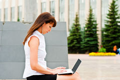 Business woman at work. Business woman working on the street with netbook Royalty Free Stock Photography