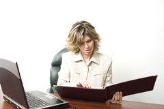 Business woman at work. With laptop and handbook Royalty Free Stock Photo
