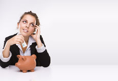 Business woman at work holding English  pound. Savings - Business woman at work holding English  pound currency  with a piggybank dreaming about her shopping Stock Photography