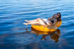 Business woman workaholic working sitting in an inflatable ring on the sea during the holidays, free space. stock photos